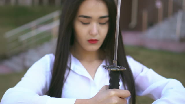 Ninja girl is looking at blade of her katana. Wind blows people's brunette hair. Ninja girl is looking at blade of her katana. Wind blows people's brunette hair. Woman is waiting for a fighting against her enemies. People is confident and strong. Japanese is balanced and powerful. ninja stock videos & royalty-free footage