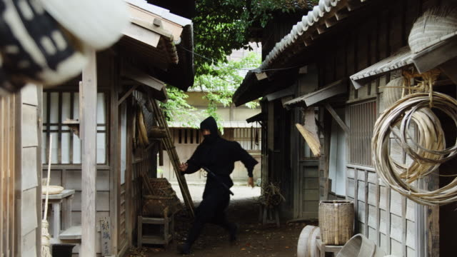 Ninja Running From Hiding Place A masked ninja sneaking around in a reconstruction of an Edo period village. ninja stock videos & royalty-free footage