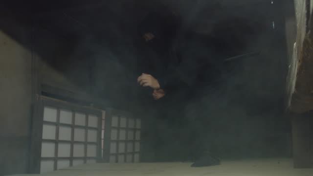 Ninja Sneaking Around in Cloud of Smoke A ninja swathed in black tiptoeing around in a cloud of smoke in a reconstruction of an Edo period village. ninja stock videos & royalty-free footage