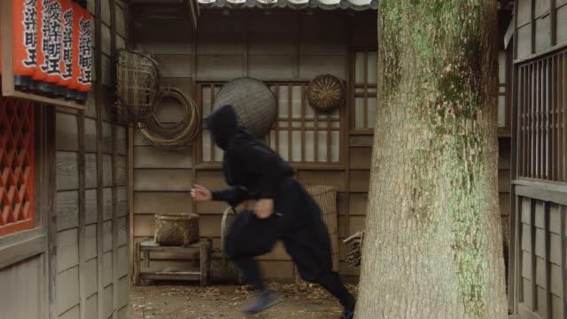Ninja Sneaking Around in Historic Village A masked ninja sneaking around in a reconstruction of an Edo period village. ninja stock videos & royalty-free footage