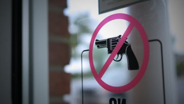 no firearms allowed in building sign on glass window - огнестрельное оружие стоковые видео и кадры b-roll