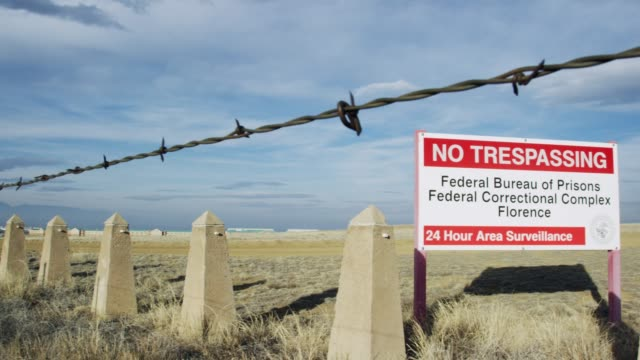 """""""no trespassing federal bureau of prisons federal correctional complex florence, 24 hour area surveillance"""" sign outside of the exterior of the united states penitentiary, administrative maximum facility supermax prison complex in florence, colorado (frem - prigione video stock e b–roll"""