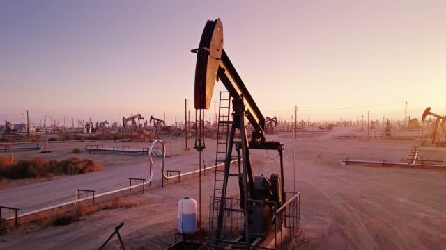 vídeos de stock, filmes e b-roll de burro com cabeça saltitante no campo de petróleo da califórnia ao pôr do sol - drone tiro - gasolina