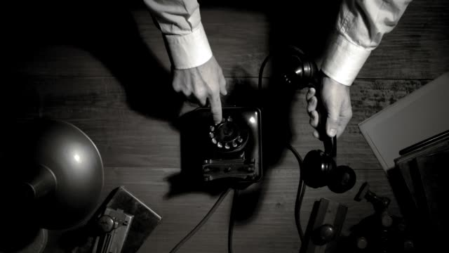 Noir film businessman making a phone call at night Noir film businessman making a phone call at night with a rotary dial telephone, suspense and thriller concept, flat lay desktop telephone receiver stock videos & royalty-free footage