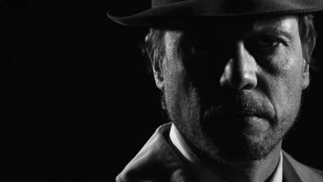 Noir film investigator standing in the dark Retro noir film character: confident investigator standing in the dark, he turns and looks at the camera detective stock videos & royalty-free footage