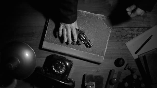 Noir film vintage agent putting the revolver on a desk Noir film 1950s vintage gangster putting his revolver and fedora hat on the desktop, thriller and crime concept, flat lay desktop detective stock videos & royalty-free footage
