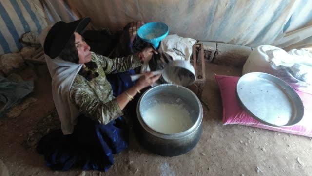 nomad frau dekantiert eine milch aus einem metallbehälter zu einer tasche von ziege gemacht - wassersparen stock-videos und b-roll-filmmaterial