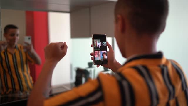 自宅でスマートフォンを使用してビデオ通話を行い、ダンスをしている非バイナリの人 - 人里離れた点の映像素材/bロール
