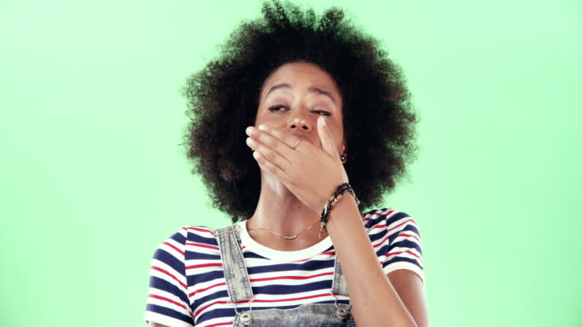 Nope, you're not holding my attention 4k video footage of a young woman yawning against a green studio background yawning stock videos & royalty-free footage
