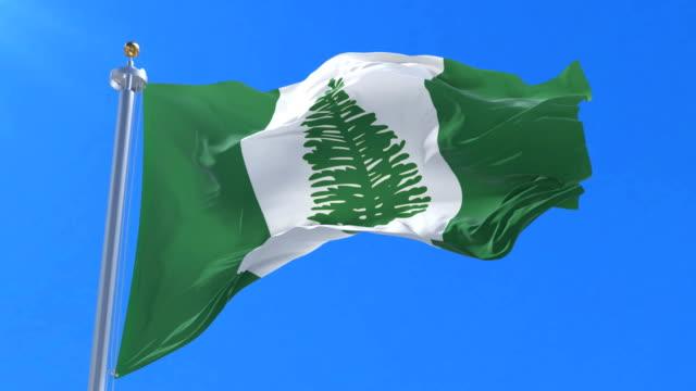 Norfolk Island flag waving at wind in slow in blue sky, loop video