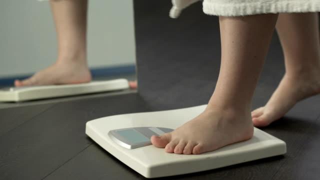 нормальный вес, девушка проверки диеты результаты на весах в домашних условиях, здоровое тело - вес стоковые видео и кадры b-roll