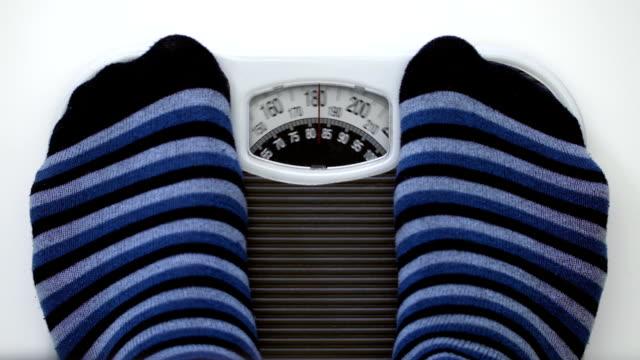 нормальная вес человек, выйдя на весы в ванной комнате - вес стоковые видео и кадры b-roll