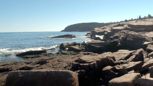CLOSE UP: North Atlantic Ocean swashing rocky coastline in Maine on sunny day