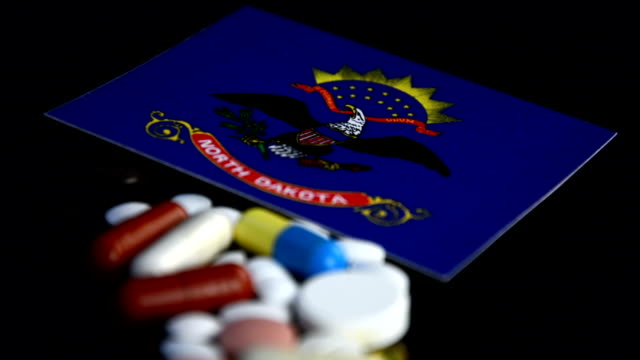 North Dakota flag with lot of medical pills isolated on black background video