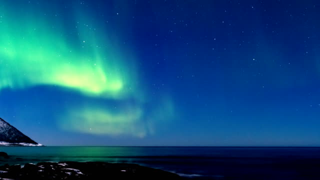 northern lights or polar light time lapse in the night sky over senja island in northern norway - nord europeo video stock e b–roll