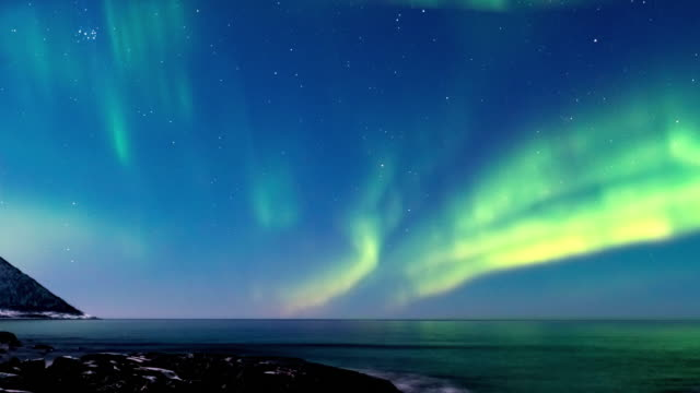 northern lights or polar light time lapse in the night sky over senja island in northern norway - aurora boreale video stock e b–roll