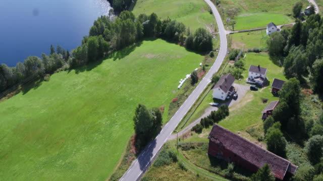 vídeos de stock e filmes b-roll de norwegian farm land with fjord in background - noruega