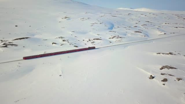 vídeos de stock, filmes e b-roll de norueguesa trem passando no meio de um vale nevado em nordland - transporte ferroviário