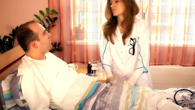 stockvideo's en b-roll-footage met neus chirurg vrouw arts onderzoekt haar patiënt man voor de operatie in het ziekenhuis - raam bezoek