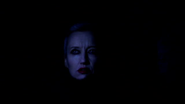 Nosferatu Lady shot of a women in the dark, with a vague unpleasant emotion on her face while a  flame is dancing in the foreground. count dracula stock videos & royalty-free footage