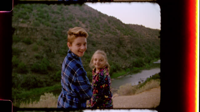Nostalgic film footage of brother and sister in bath robes looking out over the Rio Grande River and smiling at camera on family camping trip to Black Rock Hot Springs.