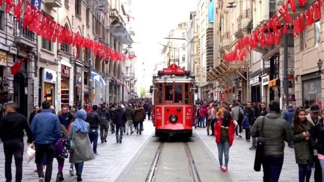 Nostalgic Red Tram in Taksim and Large crowd pedestrian people walking on Istiklal street, Istiklal Avenue one of the most famous avenues in Istanbul. 4K