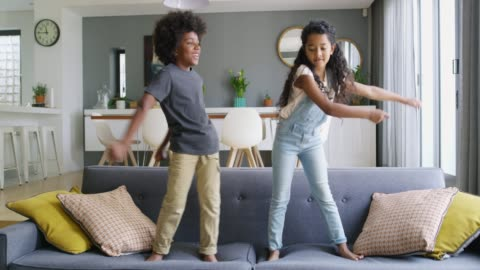 Not a care in the world 4k video footage of a young boy and girl dancing on the sofa at home child stock videos & royalty-free footage