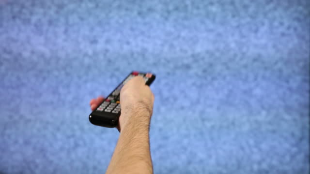 TV Not Working Hand holding a TV remote control in front of larger screen TV that is only showing static. changing channels stock videos & royalty-free footage