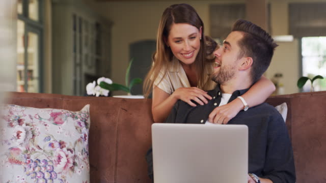 Nothing can break their connection 4k video footage of a happy young couple using a laptop on the sofa at home husband stock videos & royalty-free footage