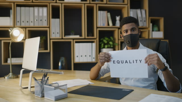 Nothing changes until we all come to the table 4k video footage of a masked young businessman holding a sign showing EQUALITY in a modern office civil rights stock videos & royalty-free footage