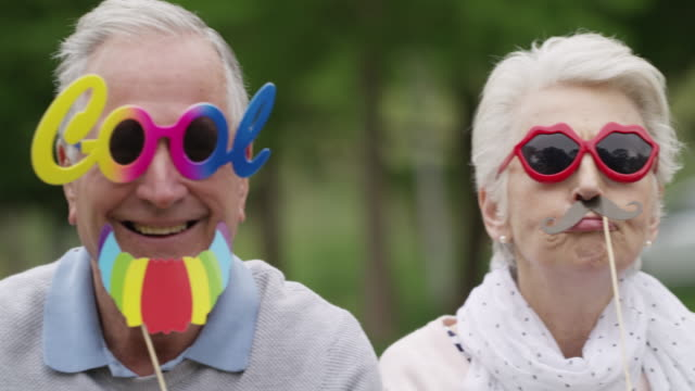 Nothing feeds the soul youthfulness like fun 4k video footage of a group of happy senior men and women wearing fun glasses at the park dressing up stock videos & royalty-free footage