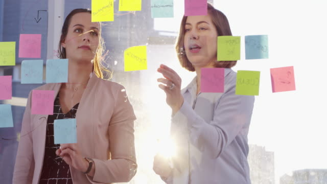 Nothing opens the door to a solution like brainstorming 4k video footage of two young businesswomen having a brainstorming session in a modern office brainstorming stock videos & royalty-free footage