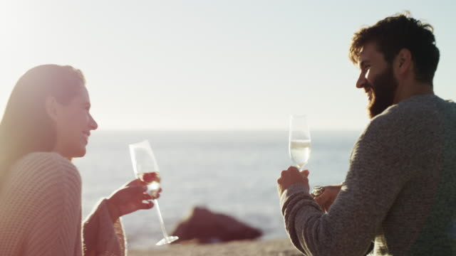 Nothing says romance like champagne at sundown 4k video footage of a happy young couple having a picnic and toasting with wine at the beach face to face stock videos & royalty-free footage