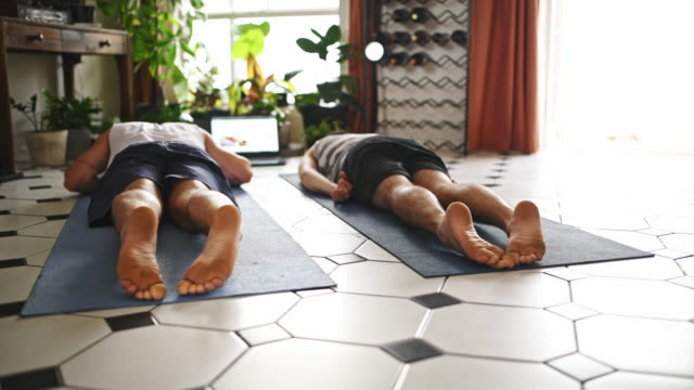 Nothing tests your strength like yoga 4k video footage of two men using a laptop while going through a yoga routine at home resting stock videos & royalty-free footage