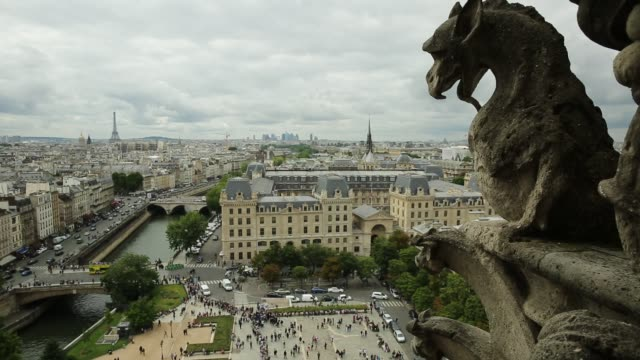 Notre Dame aerial view gargoyle statue looking the aerial view of Paris in France with the Tour Eiffel tower and Pont Saint-Michel bridge on Senna river, from top of the church Notre Dame of Paris, France. statue stock videos & royalty-free footage