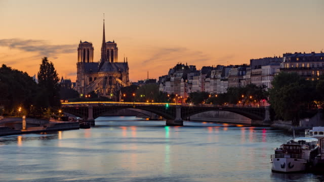 Notre Dame de Paris Cathedral and the Seine River at twilight in summer. Time-lapse, France - vídeo