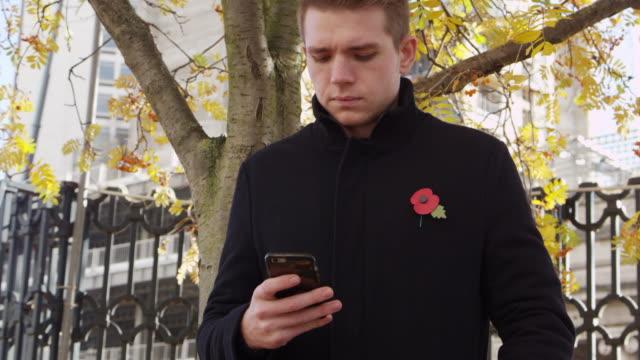 vidéos et rushes de 18 novembre 2016, birmingham/uk: homme vêtu du coquelicot du jour du souvenir à l'aide de téléphone portable - première guerre mondiale