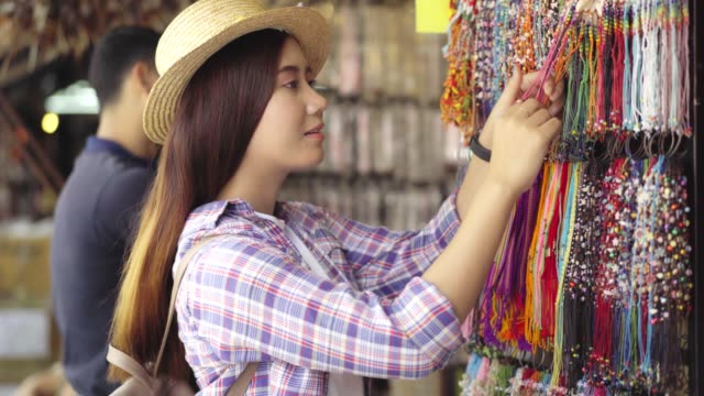November 20,2018:Bangkok Thailand ; Beautiful Asian woman shopping on the Chatuchak weekend market in the Thailand vacation choosing choosing new clothes, looking through hangers with different casual colorful garments on hangers, Shopping concept  for he video