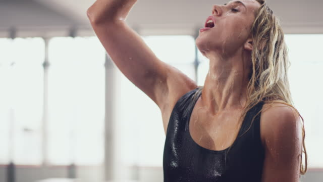 Now that's refreshing! 4k video of an attractive young woman pouring water on herself after a workout in the gym drenched stock videos & royalty-free footage