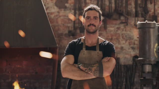 Now this is the right man for the job 4k video footage of a handsome young metal worker standing with his arms crossed in a welding workshop foundry stock videos & royalty-free footage