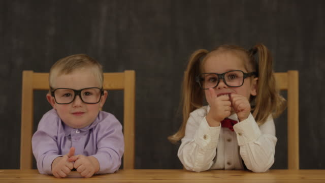 Now We Are in Business Two toddlers dressed in business clothing smile and give thumbs up to the camera in front of a blackboard. genius stock videos & royalty-free footage