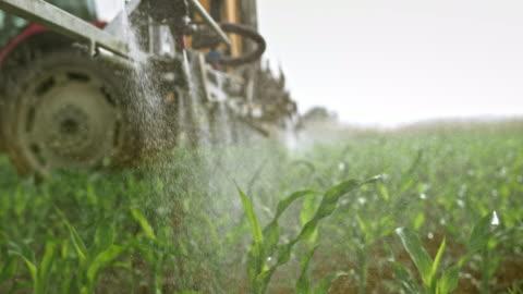 ugelli slo mo sullo spruzzatore a braccio che spruzza liquido sulle colture di mais - agricoltura video stock e b–roll