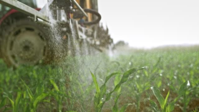 slo mo nozzles on the boom sprayer spraying liquid on the corn crops - trattore video stock e b–roll