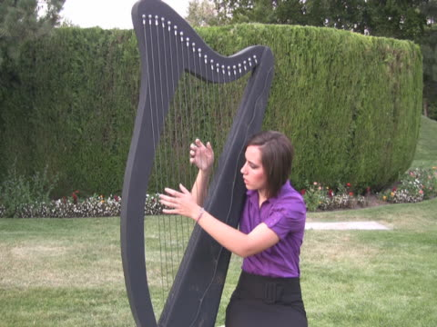 ntsc young woman playing a large harp