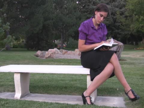vídeos de stock e filmes b-roll de ntsc jovem mulher a ler um livro no parque - só mulheres jovens