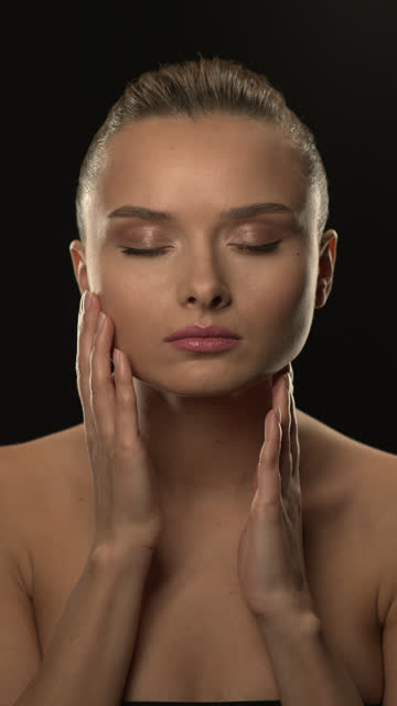 Nude girl. Close-up of the head of a beautiful brunette who touches her face with her hands with her eyes closed. video