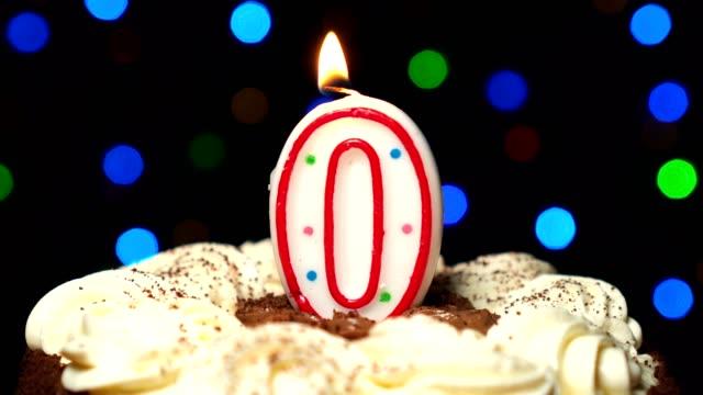 Numéro 0 sur gâteau - zéro anniversaire bougie brûle - souffler à la fin. Couleur d'arrière-plan flou - Vidéo