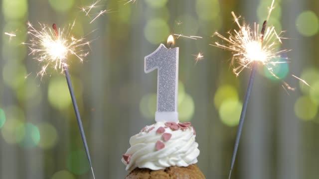 Nummer 1 Geburtstagskerze gegen ein helles Licht und goldenen Bokeh-Hintergrund – Video