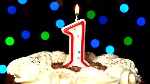 Numéro 1 sur le dessus de gâteau - un anniversaire bougie brûle - souffler à la fin. Couleur d'arrière-plan flou - Vidéo