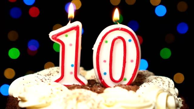 Numéro 10 sur gâteau - anniversaire dix bougies brûlant - souffler à la fin. Couleur d'arrière-plan flou - Vidéo